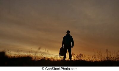 silhouette of man with backpack at sunrise in field nature -...