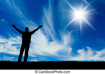 Silhouette of man with hands raised to a bright star in the...