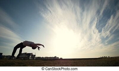 Silhouette of man workout outdoors on sunset