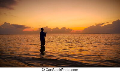 """""""Man worships with his head up to the sky and his hands together praying while standing still in the ocean during sunrise or sunset seeking the truth from a higher power, God, the Universe, or the holy spirit."""""""