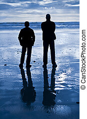 Two men stand on a wet sandy beach and look out towards the ocean. Their silhouettes are reflected on the wet sand. The image is predominantly blue and black.
