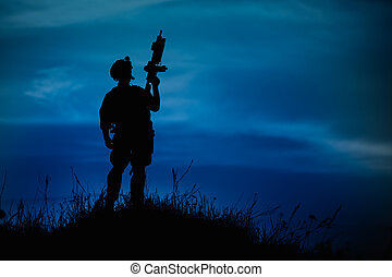 Silhouette of military soldier or officer with weapons at night.