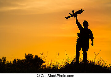 Silhouette of military soldier or officer with weapons at sunset.