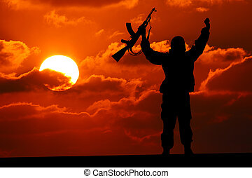 Silhouette of military soldier or officer with weapons at sunset. shot, holding gun, colorful sky, mountain, background