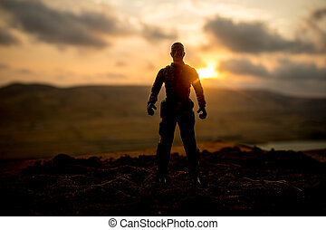 Silhouette of military soldier or officer with weapons at sunset. shot, holding gun, colorful sky, mountain, background. Decoration with toy soldier