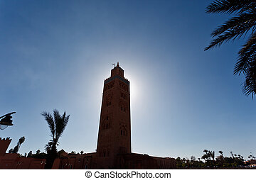 Silhouette of minaret with the sun directly behind it in a blue sky