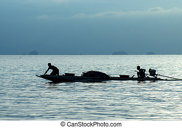 Silhouette of minimal fishing boat in the blue hour on the lake.