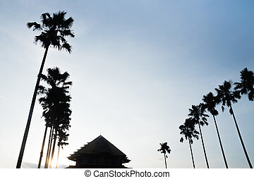 silhouette of Mosque and palm trees on blue sky