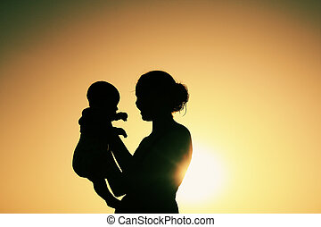 Silhouette of mother and baby at sunset