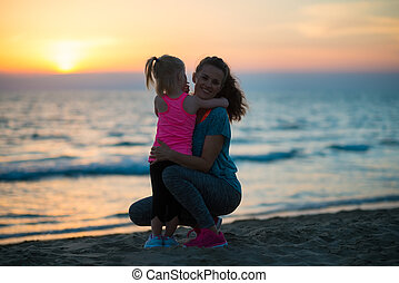 Silhouette of mother and baby girl hugging on beach