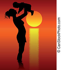 Silhouette of mother and child standing in water on a...