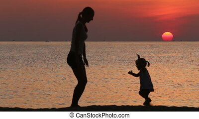 silhouette of mother and daughter doing exercises at sunrise