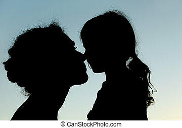 silhouette of mother and daughter touching noses, side view,...