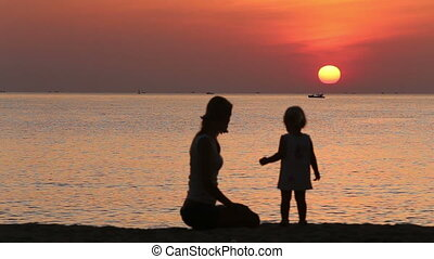 silhouette of mother and daughter admiring sunrise above sea