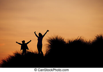 Silhouette of Mother and Son at the Beach