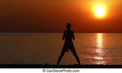 silhouette of mother doing exercises to kid on beach at sunrise