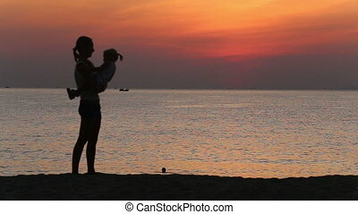 silhouette of mother doing exercises with daughter at sunrise