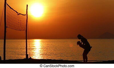 silhouette of mother doing exercises with kid at volleyball net