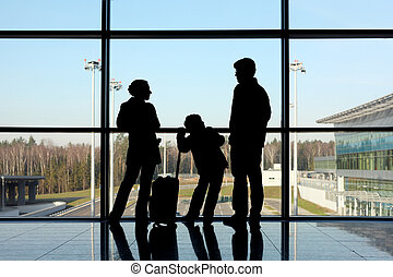 silhouette of mother, father and son with luggage standing...