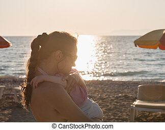 Silhouette of mother hugging baby on lonely beach