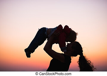 Silhouette of mother playing with baby in dusk