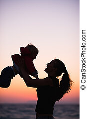 Silhouette of mother playing with baby in sunset