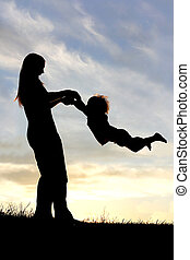 Silhouette of mother Playing with Child Outside at Sunset