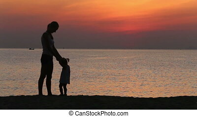silhouette of mother taking in arms daughter at sunrise