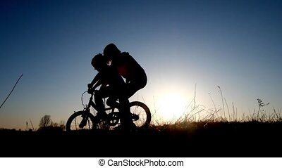 Silhouette of mother teaching her daughter to ride a bike at sunset