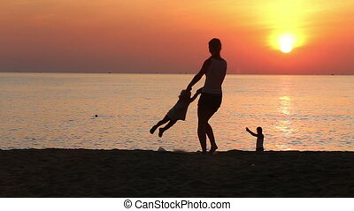 silhouette of mother turning around daughter on beach at sunrise