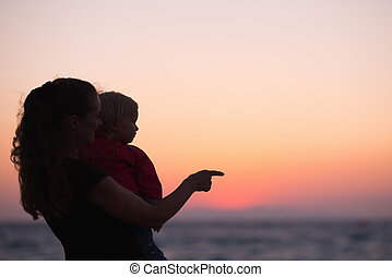 Silhouette of mother with baby in sunset pointing on copy space