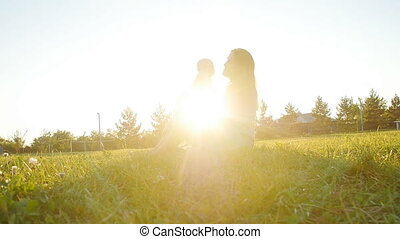 Silhouette of mother with child at sunset