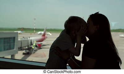 Silhouette of mother with her son standing at the window in the airport.