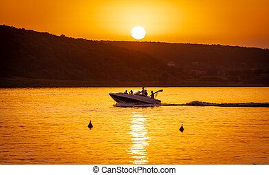 Silhouette of motorboat on the river at summer sunset