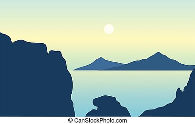 Silhouette of mountain in middle on the sea