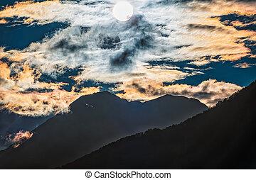 Silhouette of mountain range at orange cloudy sunset
