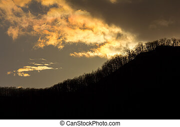 silhouette of mountains with trees against cloudy sky with the last rays of the setting sun