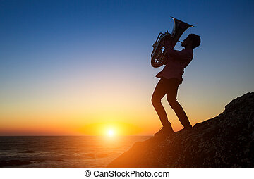 Silhouette of musician playing the trumpet on rocky sea coast during sunset. Tuba instrument.