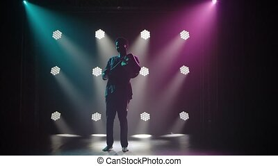Silhouette of musician plays the african talking drum yuka in a dark studio against the backdrop of lights. The black man is enjoying the music and smiling. African folklore. Slow motion