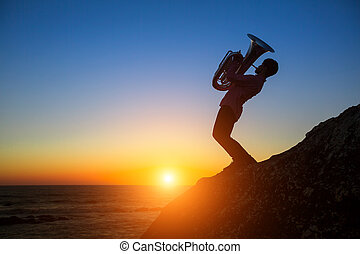 Silhouette of musician with Tuba on rocky sea coast during amazing sunset.