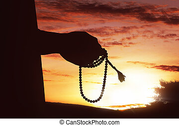 Silhouette of muslim man hand praying while holding tasbih
