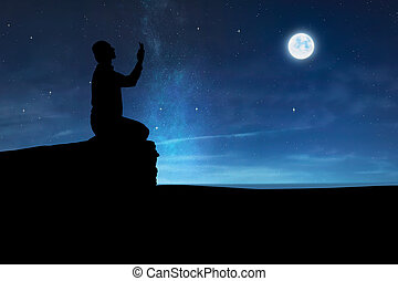 Silhouette of muslim man raising hand and praying