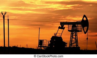 Silhouette of oil pumpjack at sunset. Oil and gas industry equipment. Motion of piston pumps. Petroleum extraction.