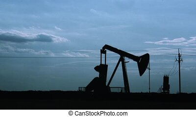 Silhouette of oil pumpjack at sunset. Motion of piston...
