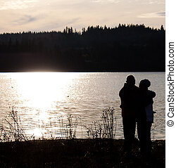 silhouette of older couple hugging.