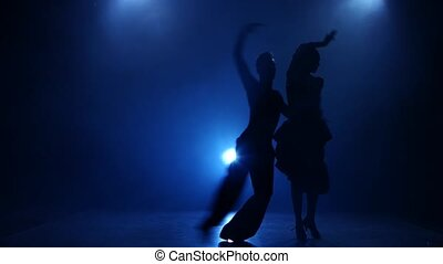 Silhouette of pair dancers performing latino dance in smoky studio