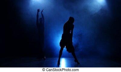 Silhouette of pair dancers performing modern dance in smoky studio