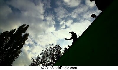 silhouette of parkour jumping girl against sky and clouds Slow Motion 400 fps