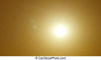 Silhouette of passenger airplane flies across sun at sunset....