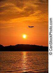 Silhouette of Passenger Airplane Landing at sunset